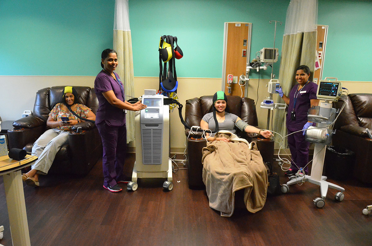 Nurses in Health City's Oncology Day Care Unit demonstrate the use of the DigniCap system