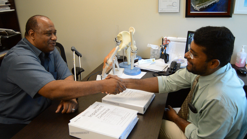 Robert Smith greets orthopedic surgeon Dr. Alwin Almeida during a follow-up visit after his surgery.